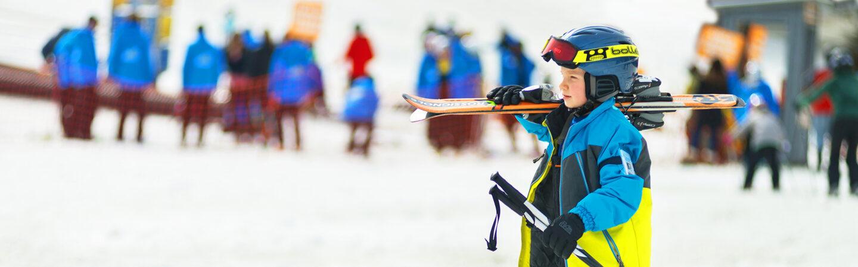 Boy carrying skis on shoulder