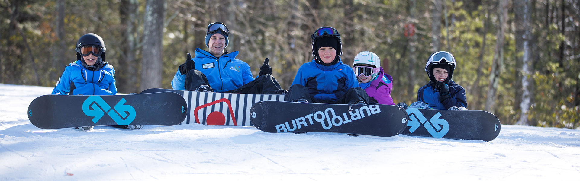 Snowboard instructor with group of students sitting on trail