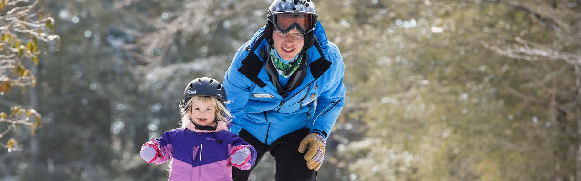 Ski instructor with puffin student on trail