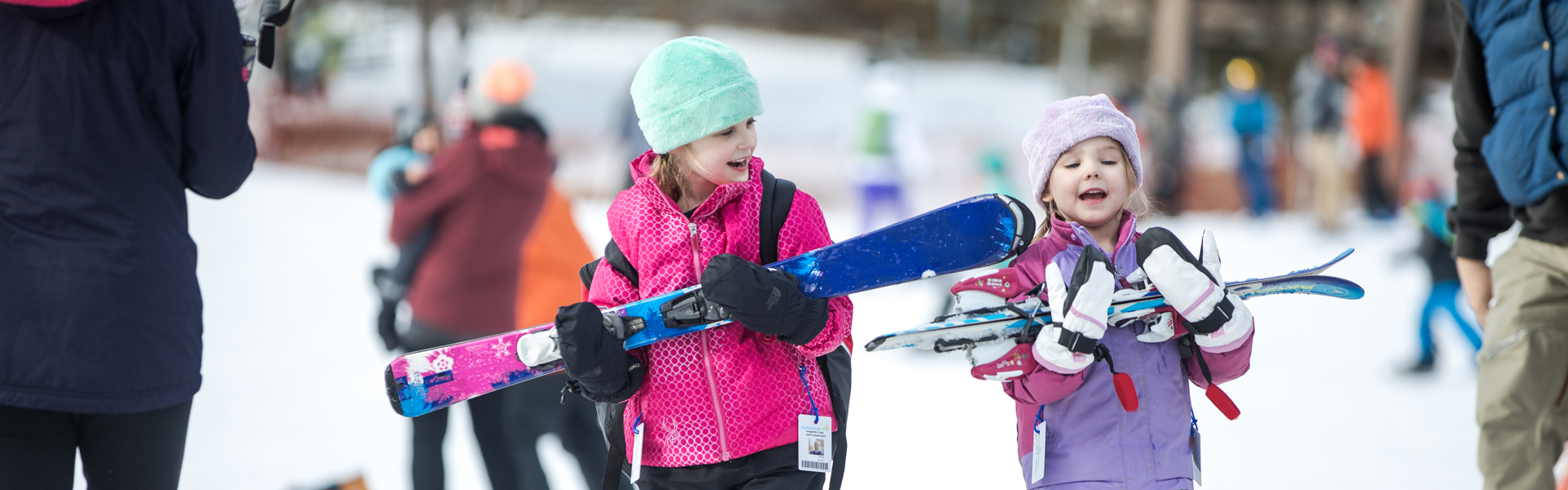 Image of two girls carrying their ski equipment