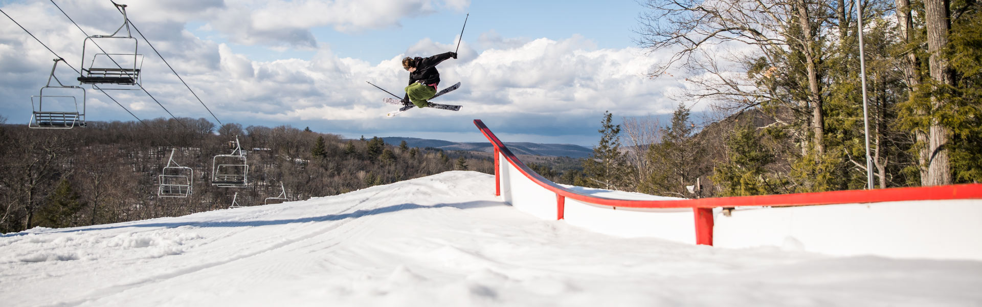 Skier jumping off terrain park feature