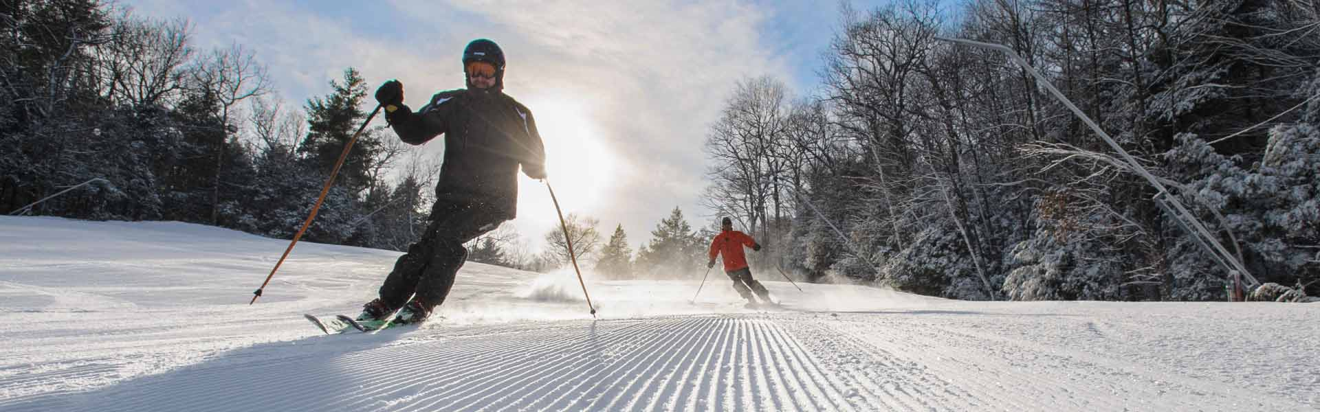 Two male skiers on groomed trail