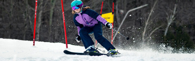 Girl skier on NASTAR race course for RTD program.