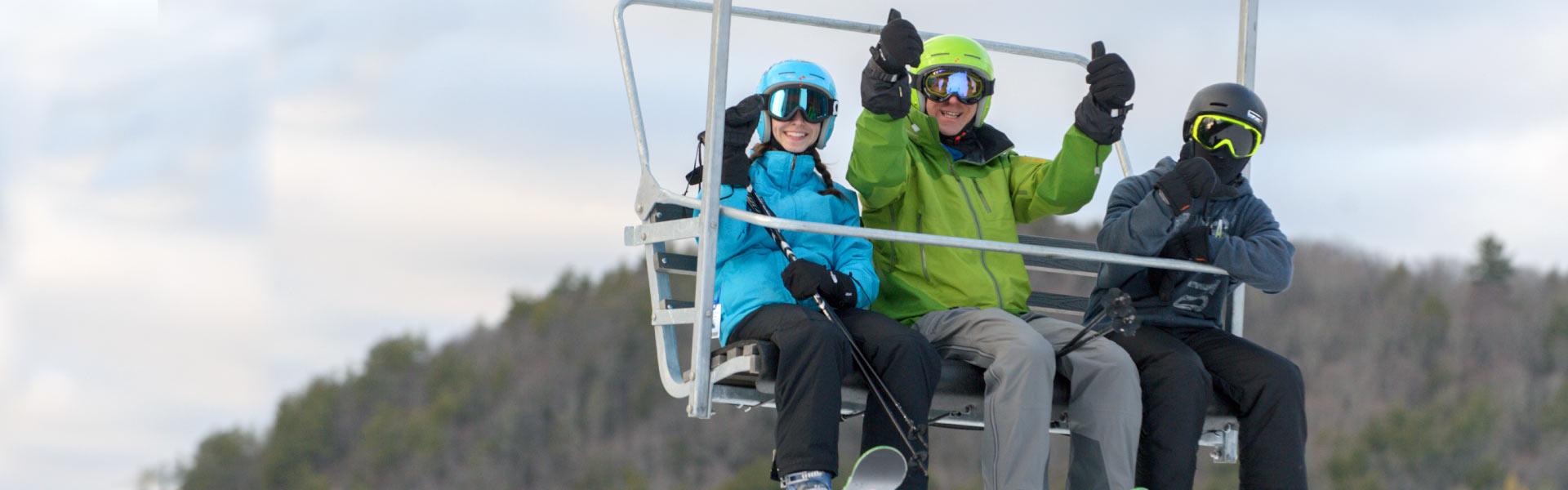 Three adults on triple chair lift