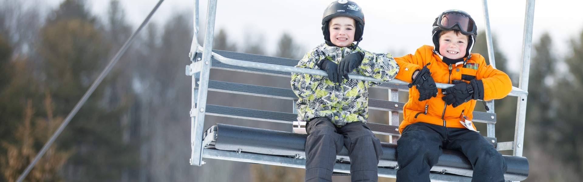 Two boys smiling on chair lift